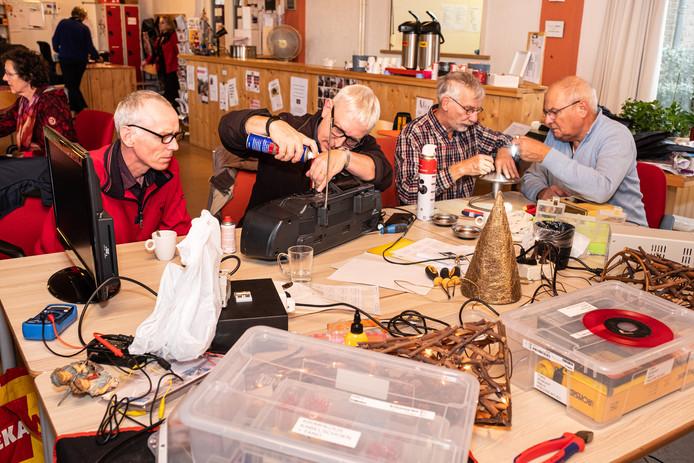 Vrijwilligers van het Repaircafé Soesterkwartier buigen zich over kapotte apparaten. Rechts Jaap Kramer.