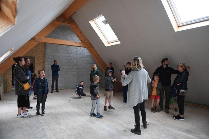 Enkele ouders met kinderen krijgen een rondleiding tijdens de Open Werfdag.