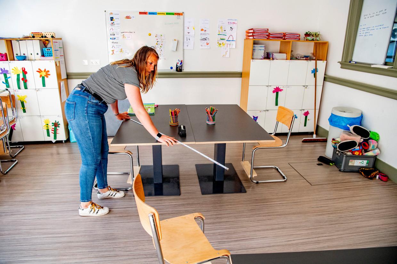 Een leraar in Rotterdam zet de tafels in het klaslokaal anderhalve meter uit elkaar. Beeld Light Rocket via Getty