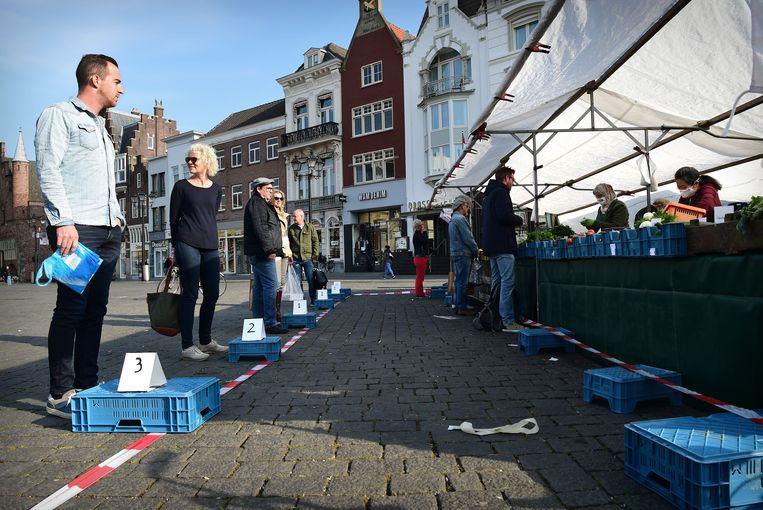 Bezoekers van de markt houden afstand tot elkaar door een door de marktkoopman verzonnen systeem.  Beeld Marcel van den Bergh / de Volkskrant