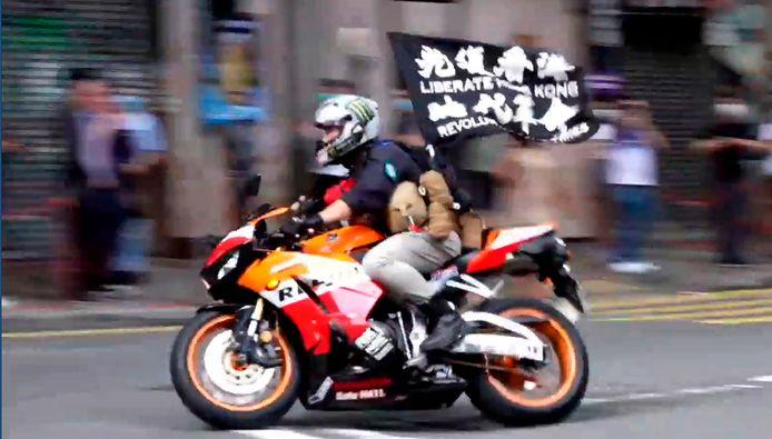 """Screenshot uit video waarin te zien is hoe Tong Ying-kit op 1 juli 2020, de dag waarop de nationale veiligheidswet in werking trad, met een motor op drie politieagenten inrijdt. Hij zwaaide op dat moment met een vlag met daarop de slogan """"Bevrijd Hongkong, revolutie van onze tijd""""."""