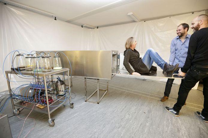 Frederik Duerinck (m) en Wander Eikelboom (r) van Sense of Smell schuiven verslaggeefster Edine in een van de kisten van de installatie die CMD-studenten hebben ontworpen om bezoekers te laten ervaren wat beroemde doden als laatste roken.