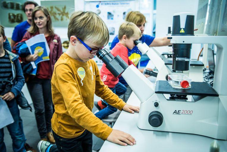 Tibe (4) en Warre Samyn (6) turen in de microscoop.