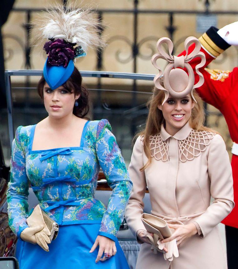 Prinses Eugenie (links) en prinses Beatrice tijdens het huwelijke van prins William en Kate Middleton. Beeld EPA