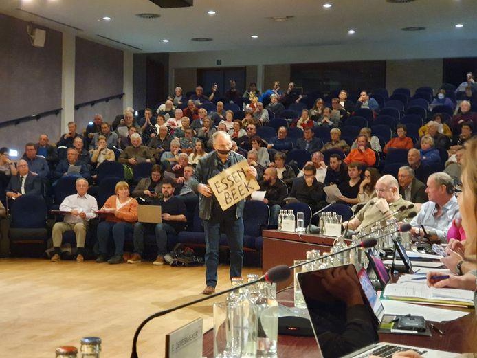 Bij de start van het debat protesteert voormalig gemeenteraadslid Eric De Greef in Halle tegen de dading die de stad en de ontwikkelaar afsluiten.