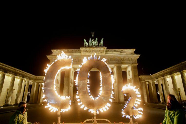Activisten van de milieuorganisatie Greenpeace protesteren met met vlammen verlichte CO2-letters voor de Brandenburger Tor tegen de klimaatverandering in Berlijn, Duitsland, donderdag 6 mei 2021.  Beeld AP