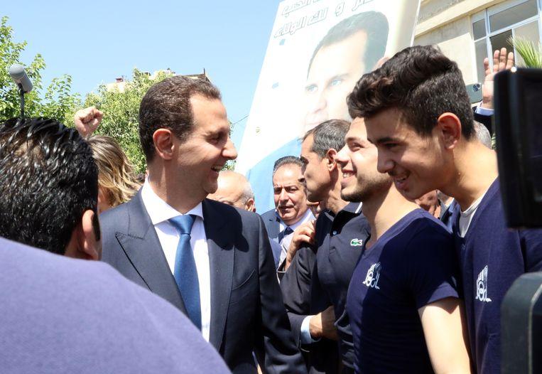 De Syrische president Bashar Assad praat vandaag met burgers nadat hij zijn stem heeft uitgebracht in een stembureau in Douma, vlakbij de hoofdstad Damascus.  Beeld Youssef Badaw / EPA