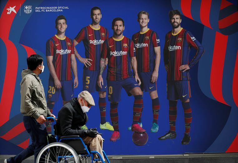 Voetgangers in Barcelona lopen langs een afbeelding van de ploeg uit de Spaanse stad. FC Barcelona is één van de krachten achter het plan voor de Super League. Beeld REUTERS