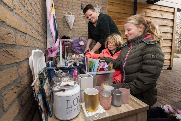 Sandra ten Hoopen (links) bij haar ruiltafel. Haar buurmeisjes Lisa (rechts) en Romy Olijve zijn vaste klanten, ze komen graag spullen ruilen.