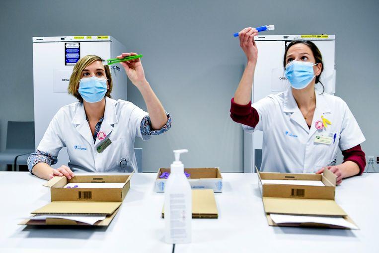 Medewerkers van het ziekenhuis in het Belgische Leuven bij het ontdooien van de vaccins van BioNTech-Pfizer. Beeld AP