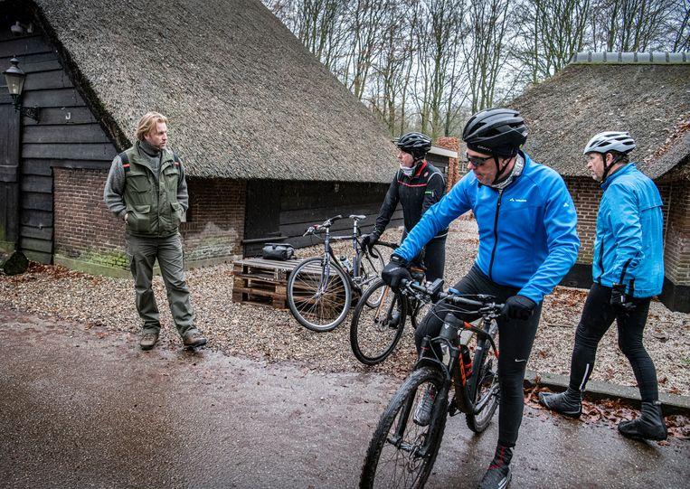 Boswachter Lennard Jasper in gesprek met fietsers op de Veluwe.  Beeld Koen Verheijden