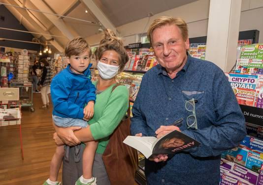 Henny Huisman signeert zijn biografie voor Dineke de Jager, hier met zoontje Joah.