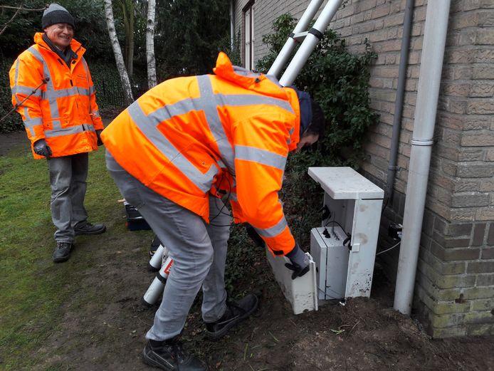 Twee medewerkers van ingenieursbureau Movares plaatsen apparatuur tegen de woning van Kees van Es aan de Spoorstraat in Dorst. Er is ook een camera gehangen, zodat de trillingen en trein gekoppeld worden.