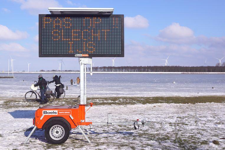 Op vrijdag 12 februari zijn op het strandje in Bunschoten tekstwagens geplaatst. Op de borden staat een waarschuwing voor het slechte ijs kwaliteit. Beeld GinoPress B.V.