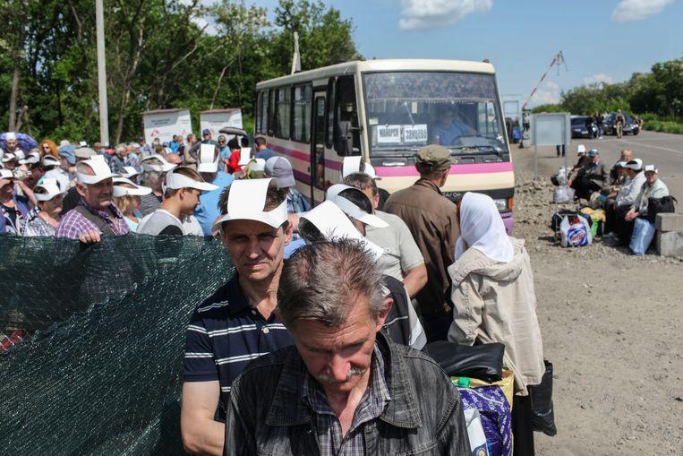 Wachtenden bij het checkpoint Zajtseve. Elke dag proberen zo'n 20 duizend mensen de frontlinie over te steken bij een klein aantal checkpoints. De wachttijden zijn soms langer dan 24 uur. Sanitaire voorzieningen en drinkwater ontbreken aan de kant van de rebellen. Beeld Oleksandr Tetsjynski