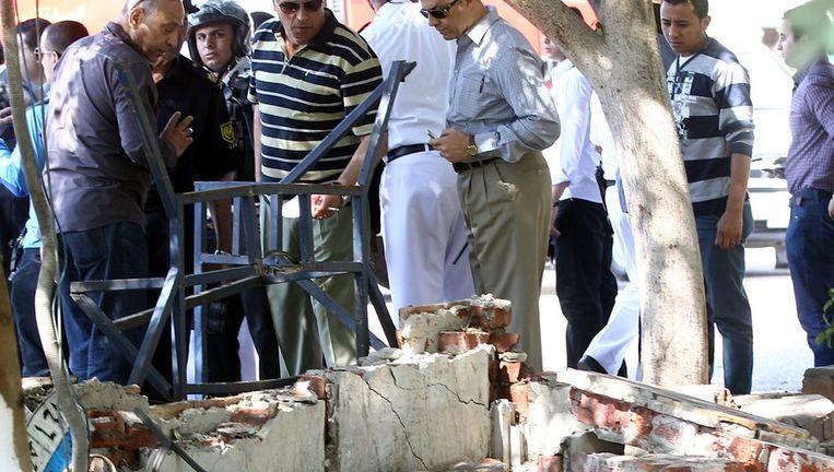Veiligheidsagenten inspecteren de plaats van de bomaanslag in Caïro Beeld EPA