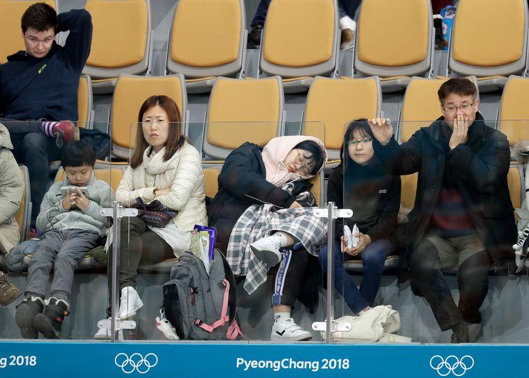 Een toeschouwer valt in slaap tijdens een curlingwedstrijd. Beeld AP