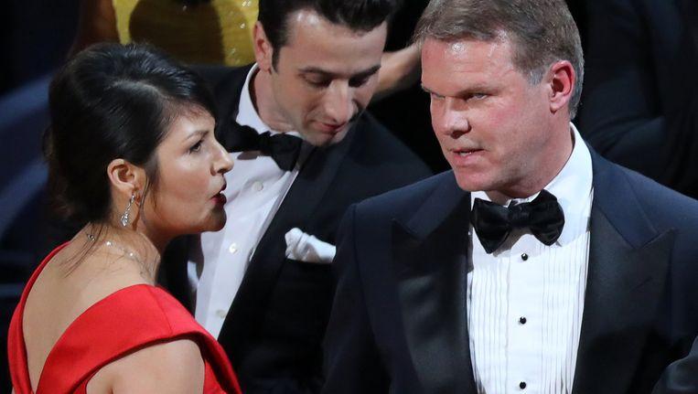Martha Ruiz (links) en Brian Cullinan (rechts) van PricewaterhouseCoopers overleggen op het podium nadat 'La La Land' verkeerdelijk de Oscar voor beste film kreeg toegekend. Die prijs was immers voorzien voor 'Moonlight'. Beeld REUTERS