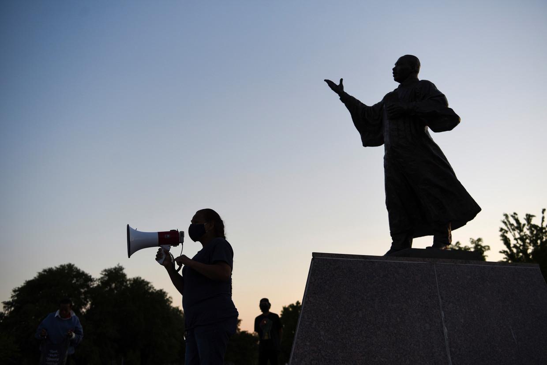 Een vrouw spreekt een menigte toe voor het standbeeld van Martin Luther King in Houston, Texas.  Beeld REUTERS