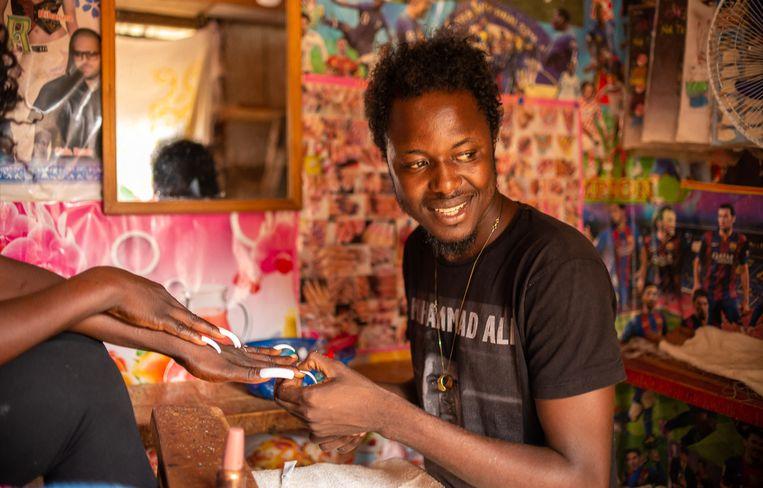 Debonheur Kol helpt een klant in zijn zaak in Bangui, de hoofdstad van de Centraal Afrikaanse Republiek. In het land werken steeds meer mannen als manicure en pedicure om geld te verdienen. In het op een na armste land ter wereld zijn er door de burgeroorlog nauwelijks banen. De werkloosheid bedraagt meer dan 24 procent.  Beeld AFP