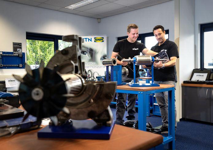 Leerling-monteur Mark van der Zanden (links) en directielid Harm van Stiphout bij een trainingsopstelling voor het demonteren en monteren van een lager van een machine.