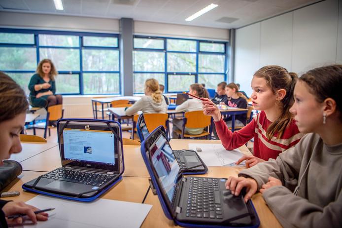 De geschiedenisles met docente Sanne van den Dries (zittend links achterin). Terwijl een deel van de klas naar haar luistert, werken andere leerlingen zelfstandig aan hun opdracht.
