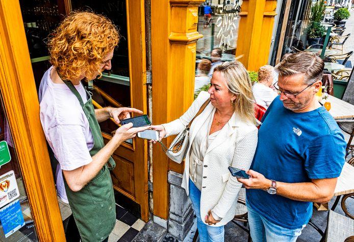 Een horecamedewerker controleert het toegangsbewijs van gasten.