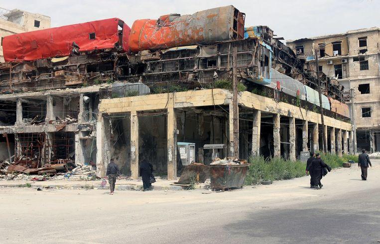 Opgestapelde bussen op een gebouw dienen als bescherming voor burgers tegen de troepen van President Assad in Aleppo, april 2015. Beeld reuters