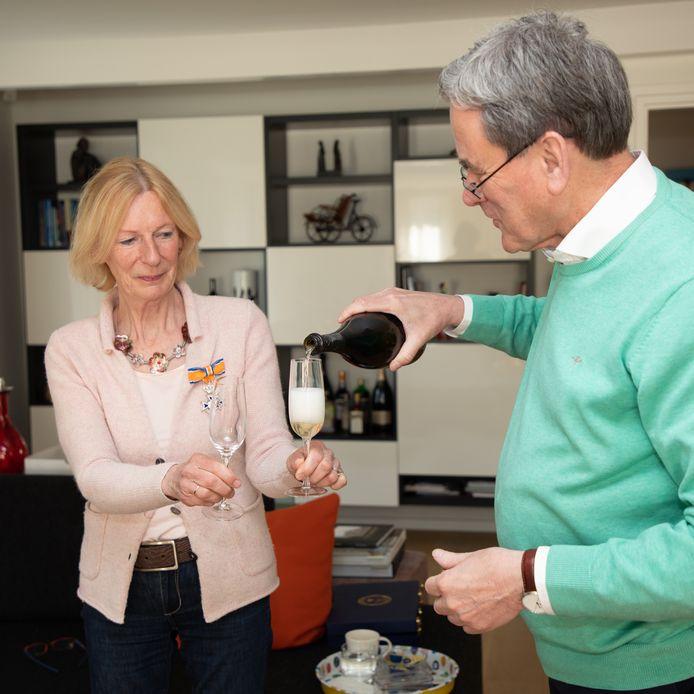 Jos Burgers schenkt champagne in voor zijn vrouw Julia, geridderd in Oisterwijk.