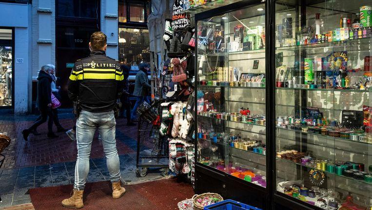 Op de Nieuwendijk is de politie een souvenirwinkel binnengevallen. Een agent houdt de wacht bij de ingang Beeld Dingena Mol