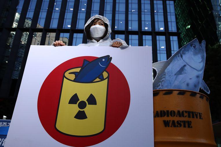 Een betoger in Seoul protesteert voor de Japanse ambassade tegen het lozen van radioactief water in zee door Japan. Beeld Getty Images