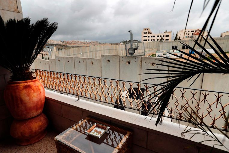 A picture taken from the balcony of one of the rooms at street artist Banksy's newly opened Walled Off hotel in the Israeli occupied West Bank town of Bethlehem, on March 3, 2017, shows Israel's controversial separation wall. Secretive British street artist Banksy opened a hotel next to Israel's controversial separation wall in Bethlehem on Friday, his latest artwork in the Palestinian territories.  / AFP PHOTO / THOMAS COEX Beeld null