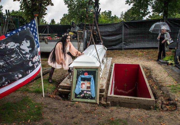 De kist van de onlangs overleden Cor Vermeulen op begraafplaats Zuylen wordt onder toeziend oog van zijn dochter Lisa-Marie (l) en vrouw Willeke verplaatst naar een tijdelijk onderkomen. De grafkelder was door hevige regenval gaan drijven en moet worden hersteld.
