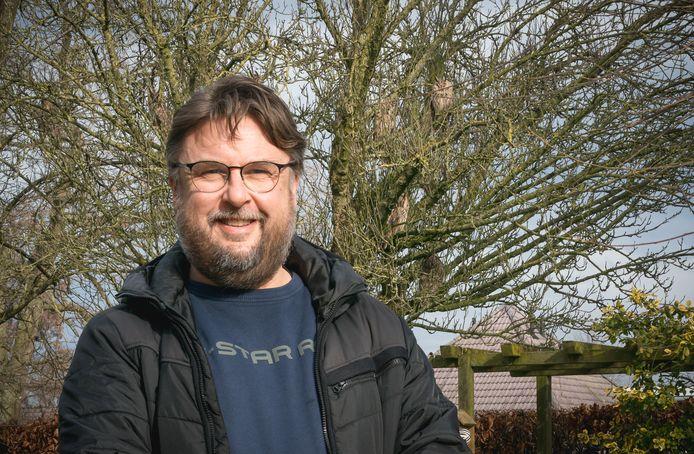 Nico Veenendaal met op de achtergrond enkele van de uilen in de boom.