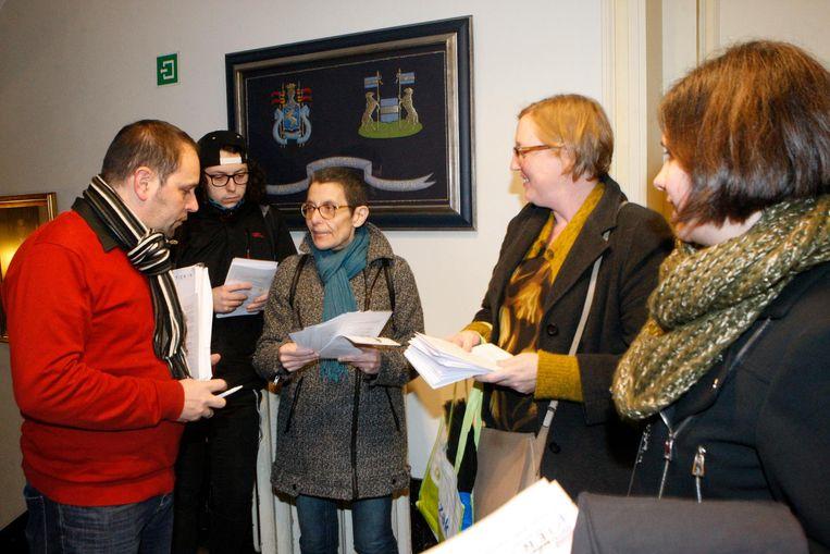 Enkele actievoerders delen flyers uit aan de gemeenteraadsleden.