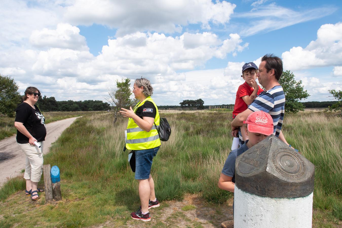 Archeologiedag in Riel. Een archeoloog geeft uitleg tijdens een rondleiding aan een gezin.