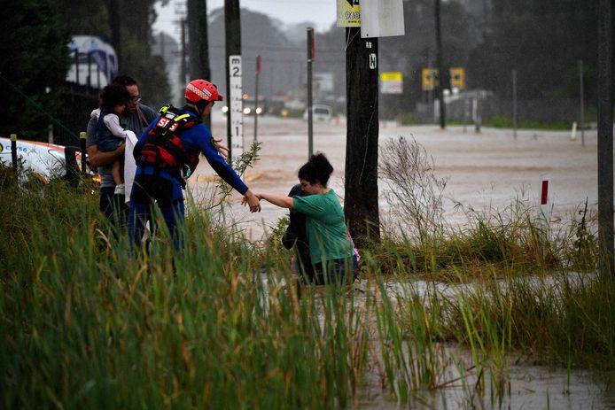 Een reddingswerker helpt een inwoner uit het water van een ondergelopen straat  in de buurt van Sydney. (20/03/21)