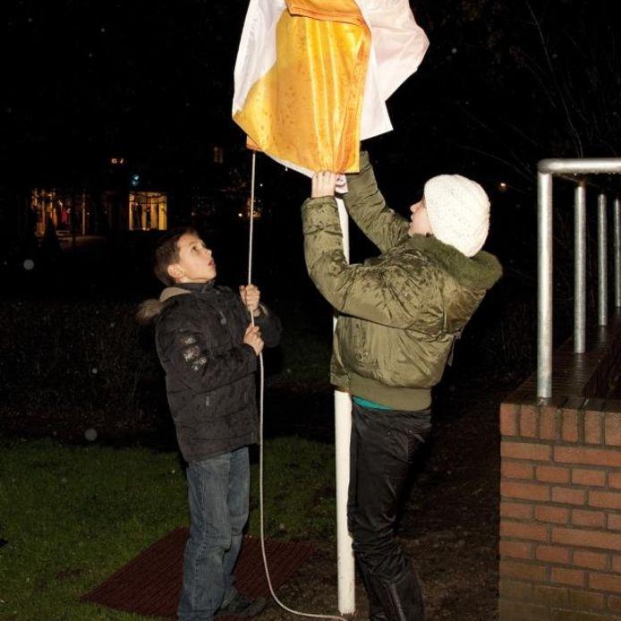 Marnix en Felice hijsen de vlag met het logo van De Brug, het nieuwe gefuseerde protestantse kerkgenootschap. foto Mark Neelemans