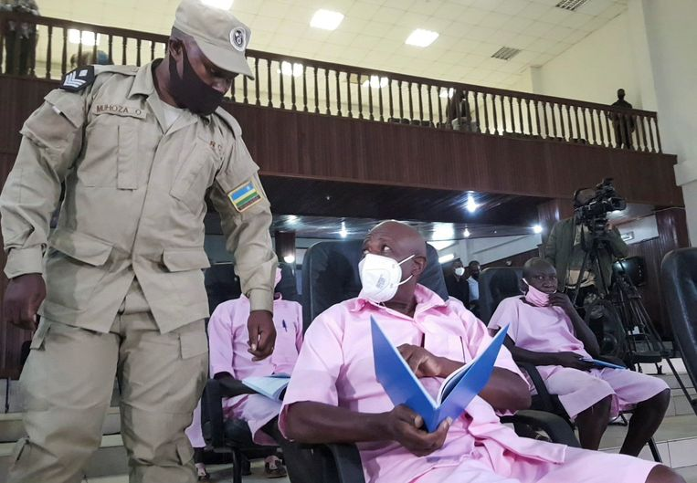 Paul Rusesabagina, met medeverdachten en een bewaker naast zich in de rechtszaal vorige week in Rwanda.  Beeld Reuters