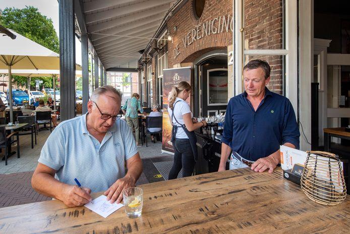 Gerard Kerkhoff (rechts) kijkt toe als na de eerste lockdown een gast zich registreert. Foto: Gerard Burgers