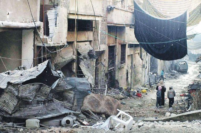 Homs, 1 januari: kinderen in een belegerde wijk. Uitgehangen gordijnen moeten sluipschutters het zicht benemen. Beeld reuters