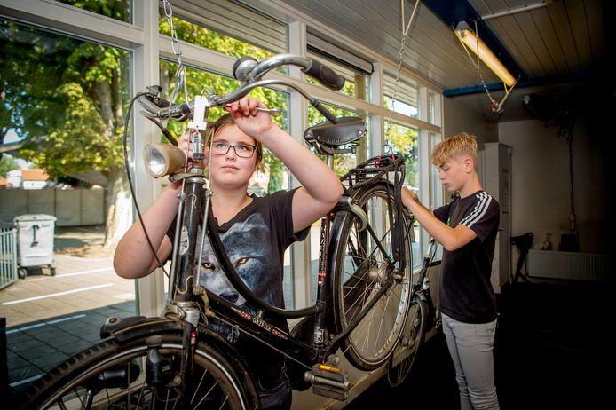 Leerlingen Sanne en Rafaël sleutelen aan een fiets in het fietspoetsstation van het Pro College in Wijchen.