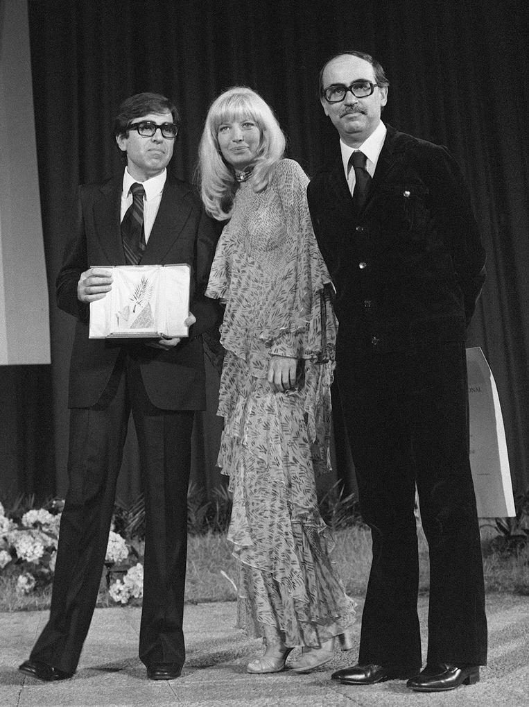 Italiaanse actrice Monica Vitti overhandigt de Palme D'or aan de broers Vittorio (R) en Paolo Taviani, voor hun film Padre Padrone. Beeld AFP