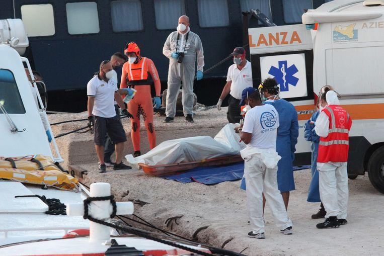 Het levenloze lichaam van een migrant wordt eveneens van boord gehaald. Beeld AFP