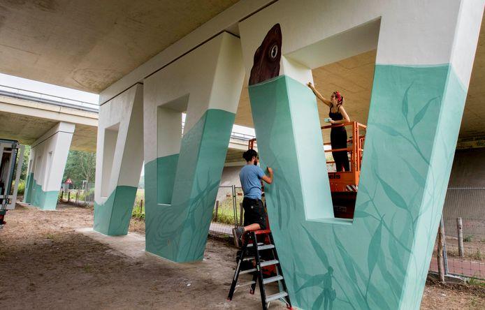 Jori van Boxtel en Remco Weismann brengen het kunstwerk aan op de pijlers van het viaduct A58 aan het Bels Lijntje