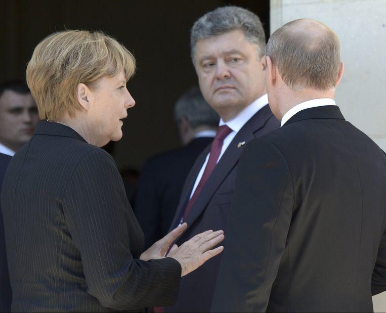 De Oekraïense president Petro Porosjenko (midden), met zijn Russische ambtgenoot Poetin (r) en de Duitse bondskanselier Merkel. Beeld reuters
