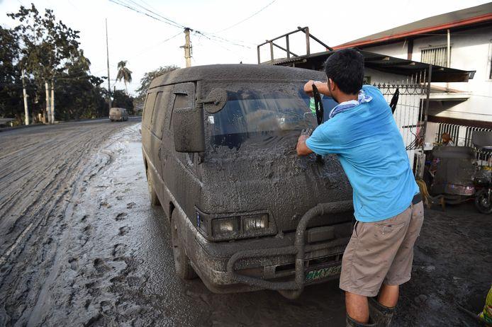 Auto's en straten liggen bedekt onder een dikke laag van as en modder.