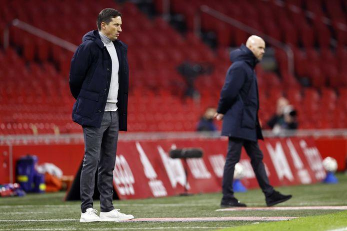 PSV-trainer Roger Schmidt en Erik ten Hag (Ajax) kijken geconcentreerd naar de verrichtingen op het veld.