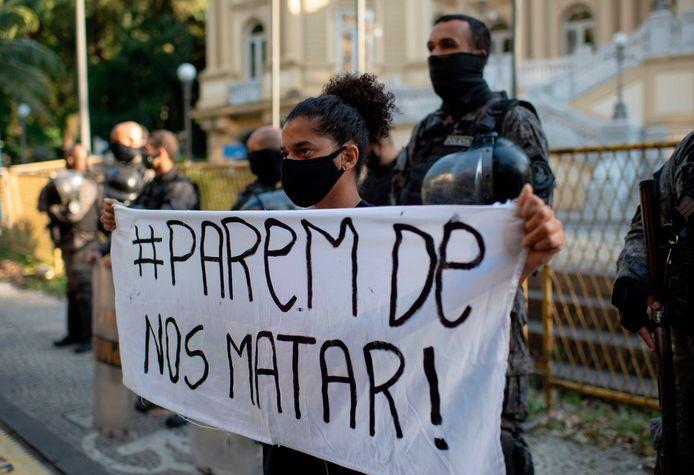 Een vrouw in Rio de Janeiro met een spandoek met de tekst 'Houd op ons te vermoorden'.