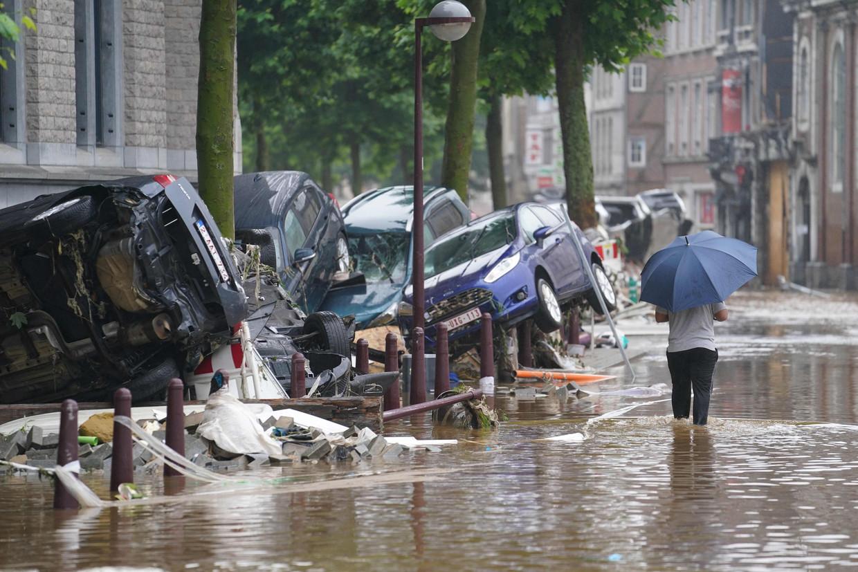 Een inwoner van Verviers, bij Luik in België, waadt door de ondergelopen straten. 'Kom maar op met die zielige plaatjes van dieren en mensen', zegt filosoof Bas Haring. 'Het zorgt ervoor dat mensen rampen serieuzer nemen.' Beeld AFP